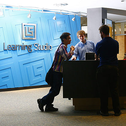 Students talking at the check-in desk for the learning studio in the ACU Brown Library