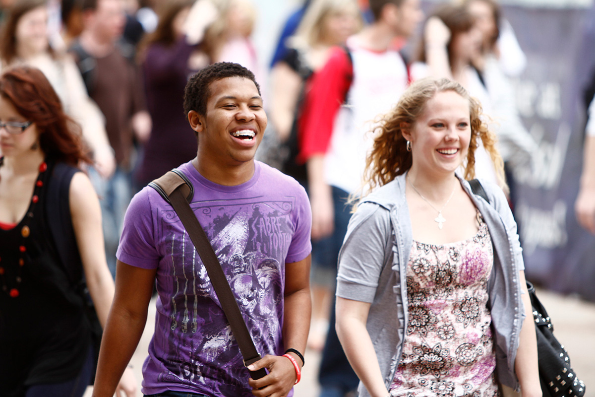 Male and female student walking through campus, laughing and talking