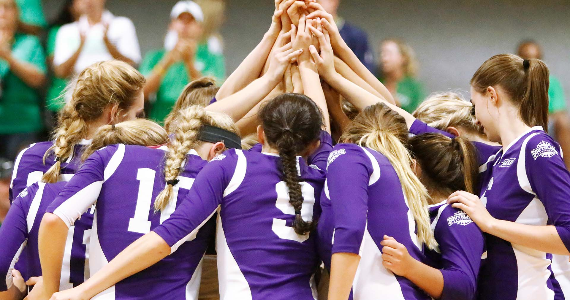 ACU women's volleyball players in a huddle