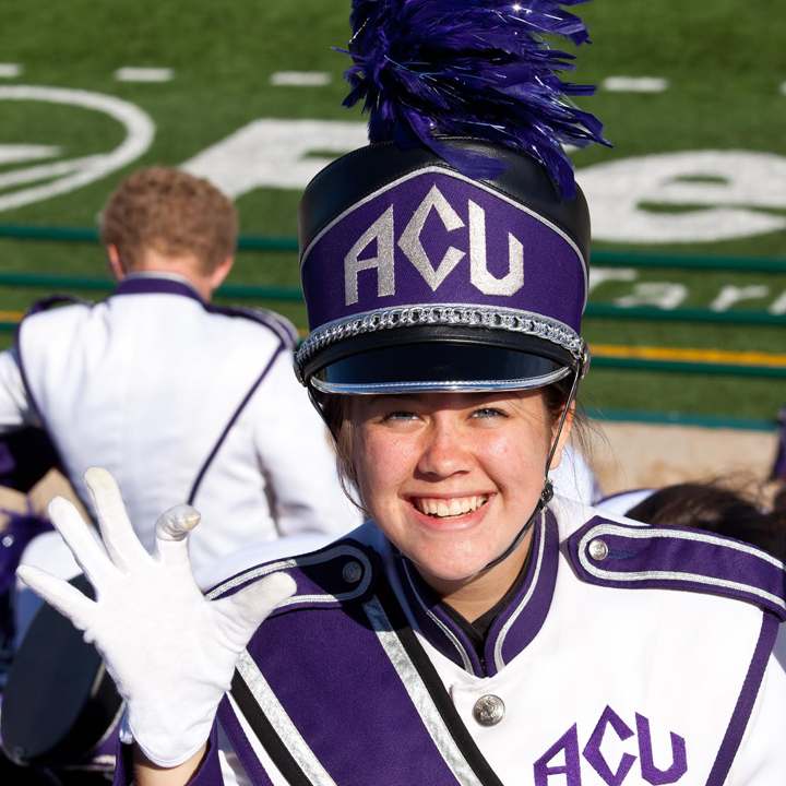 ACU marching band student holding up the Wildcat hand sign