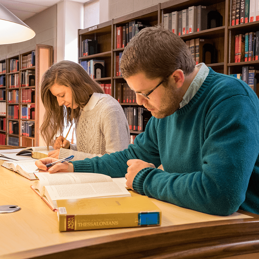 Male and female students studying in the library.