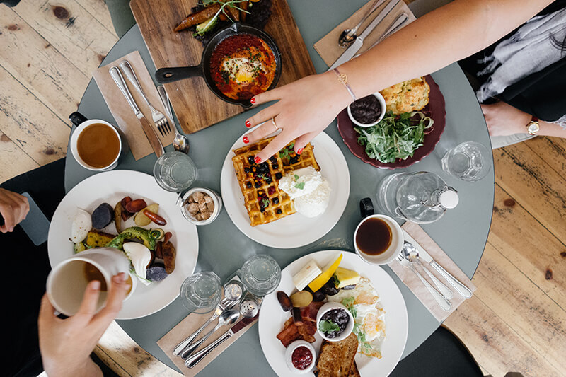 Brunch on a table with a female reaching for the waffles