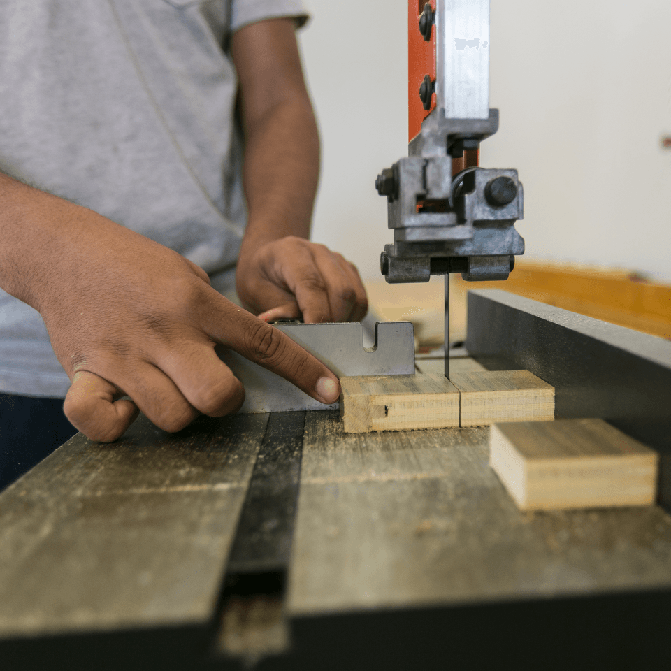 Student working in the engineering lab, using a wood cutting machine
