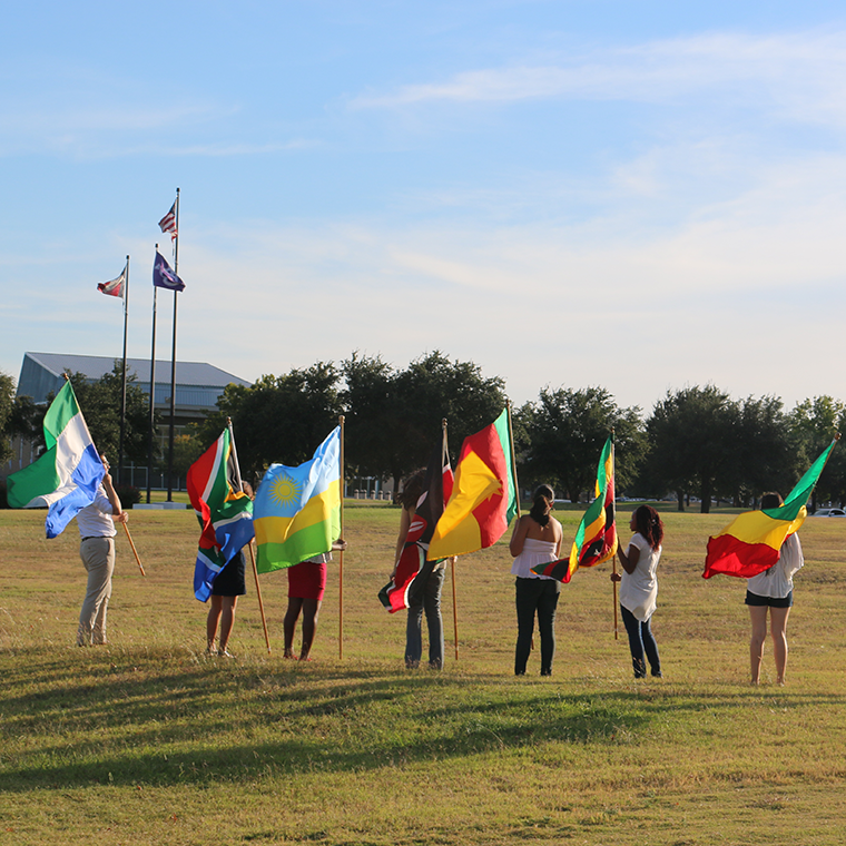 Students holding international flags at the front entrance to campus