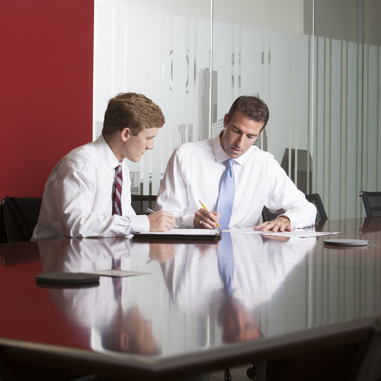 Two male business managers sitting at a table discussing plans.