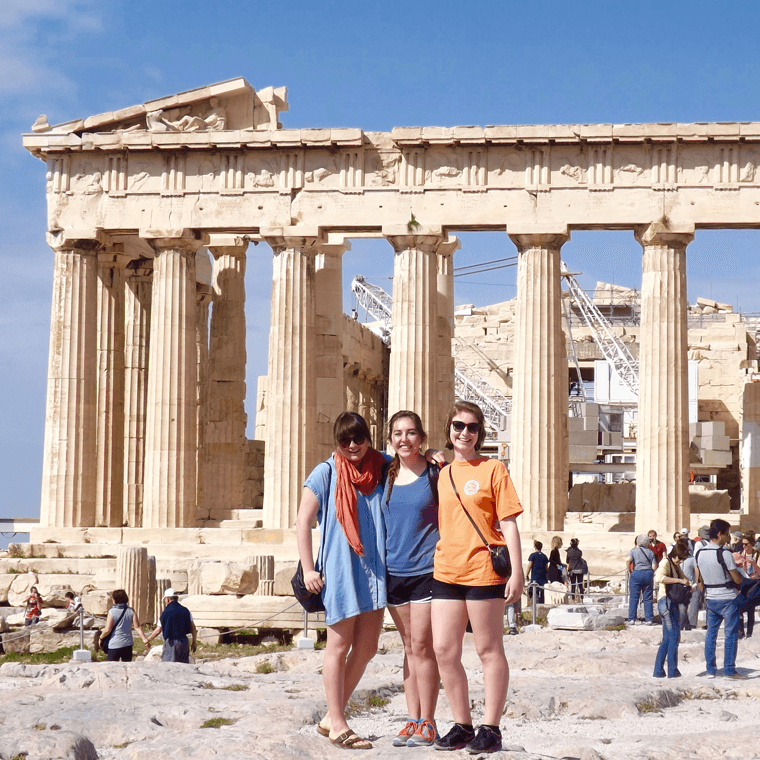 Three female students on a study abroad trip touring ruins of Rome