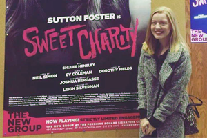 Ally Beans standing next to a poster for Sweet Charity