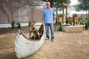 Geoffrey Broderick next to his storybook sculpture