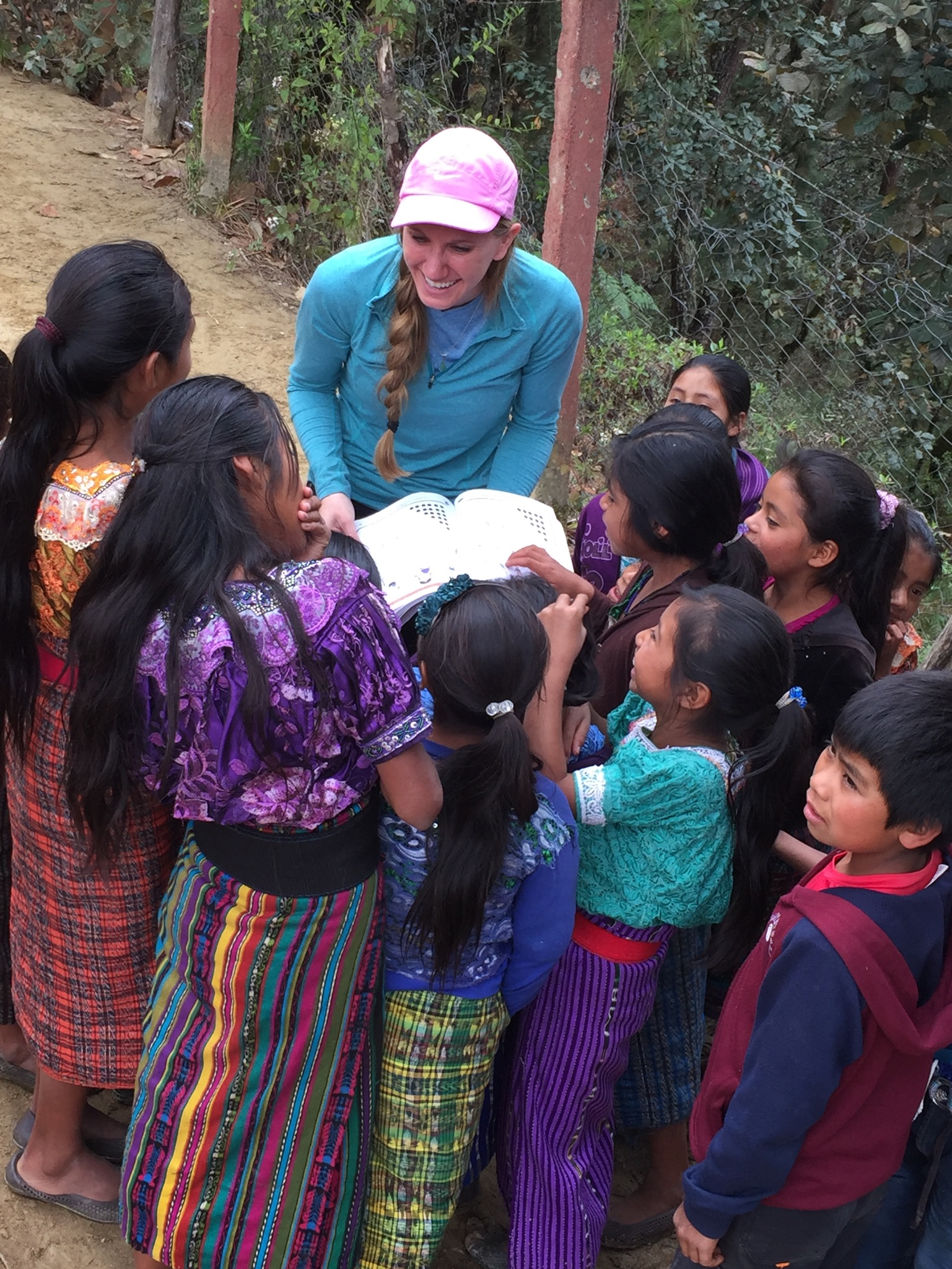 Female student reading a book to children while on a missions trip with ACU