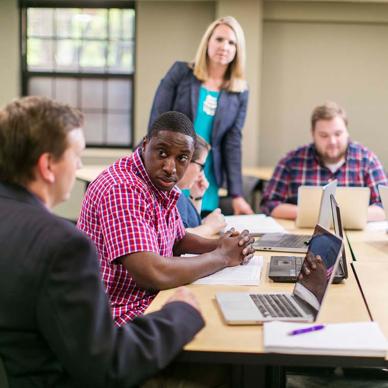 Graduate students sitting at a table discussing topics with their professor who is standing up