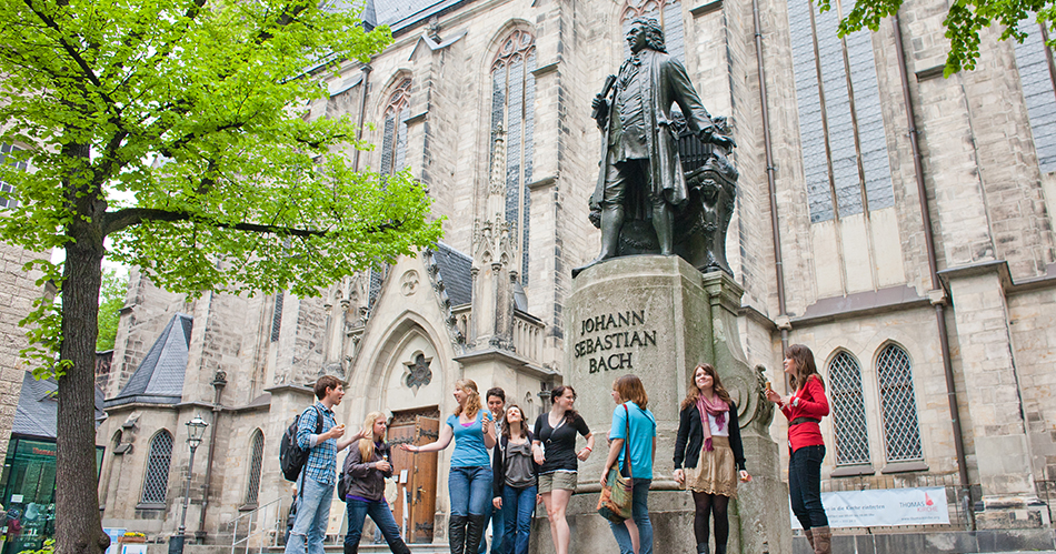 Students touring St. Thomas Church in Leipzig and taking pictures in front of the Johann Sebastian Bach statue