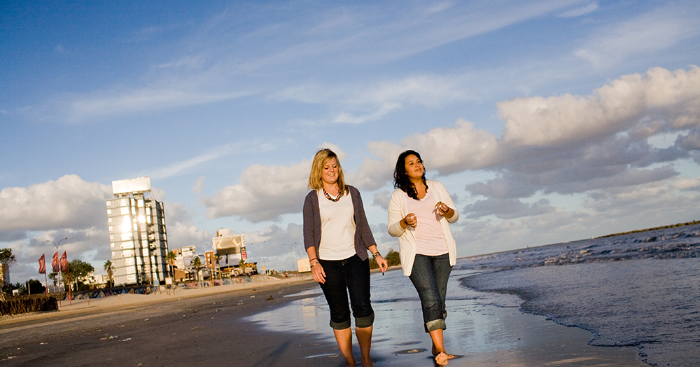 Two female students walking the beach in Montevideo on their study abroad trip