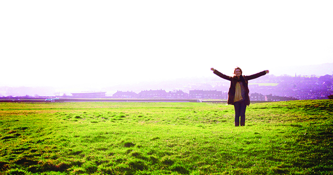 Female student on study abroad in Oxford standing in a field with arms spread open